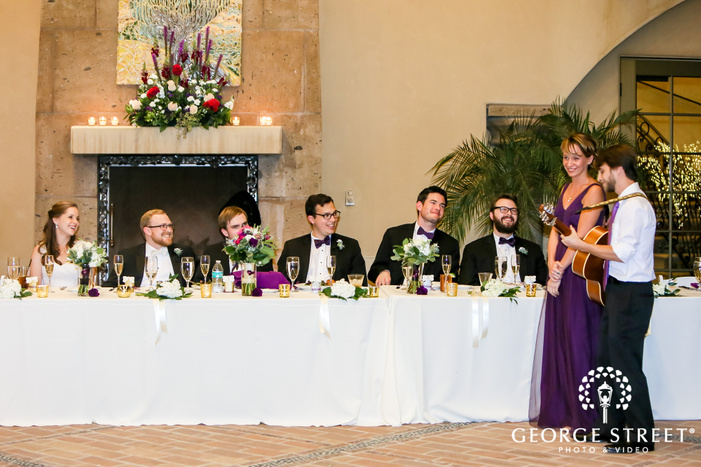 groomsman playing guitar during reception toast