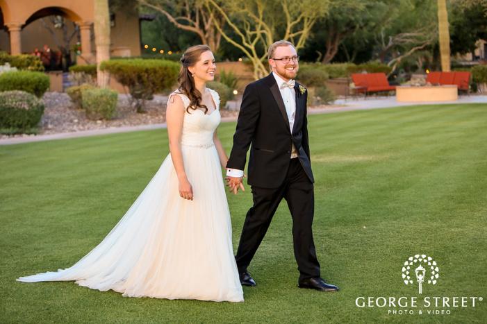 ravishing bride and groom walking in yard
