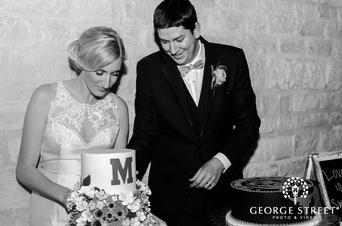 cheerful bride and groom at cake cutting ceremony