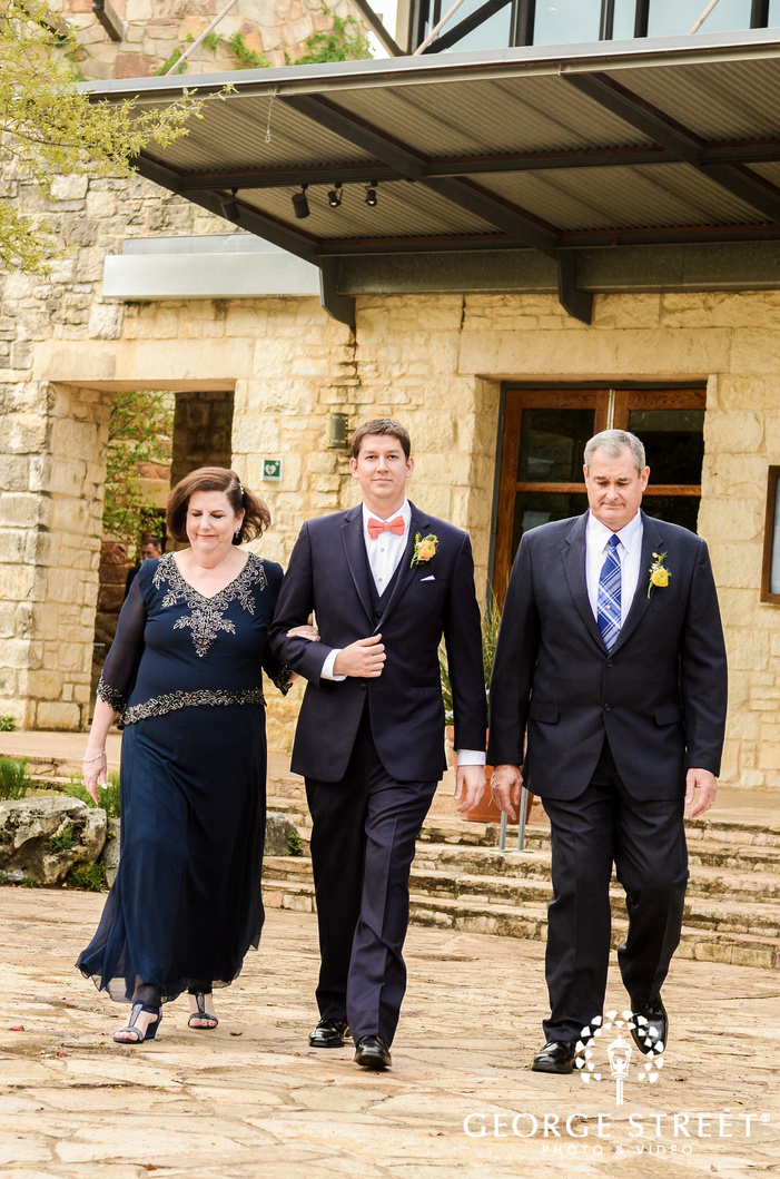 joyful groom and parents walking down the aisle