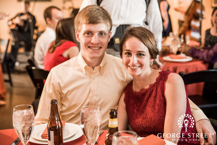 cheerful guests at reception table wedding photos