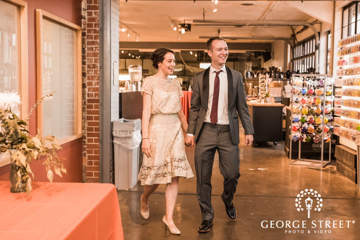 excited bride and groom entrance in reception at third degree glass factory in st  louis wedding photo