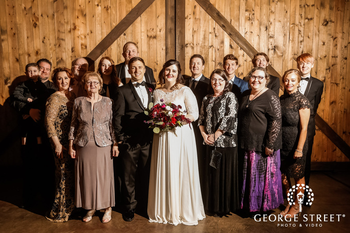 charming couple and guests in barn wedding photo