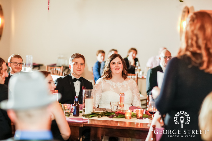 happy couple on reception table wedding photo