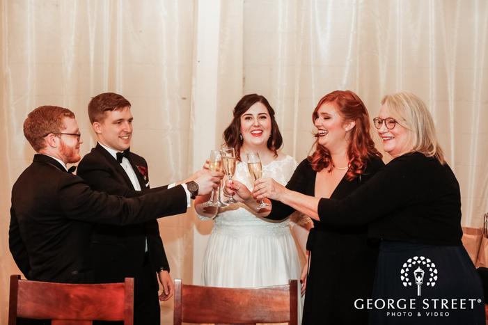 joyous couple and guest wedding toast wedding photo