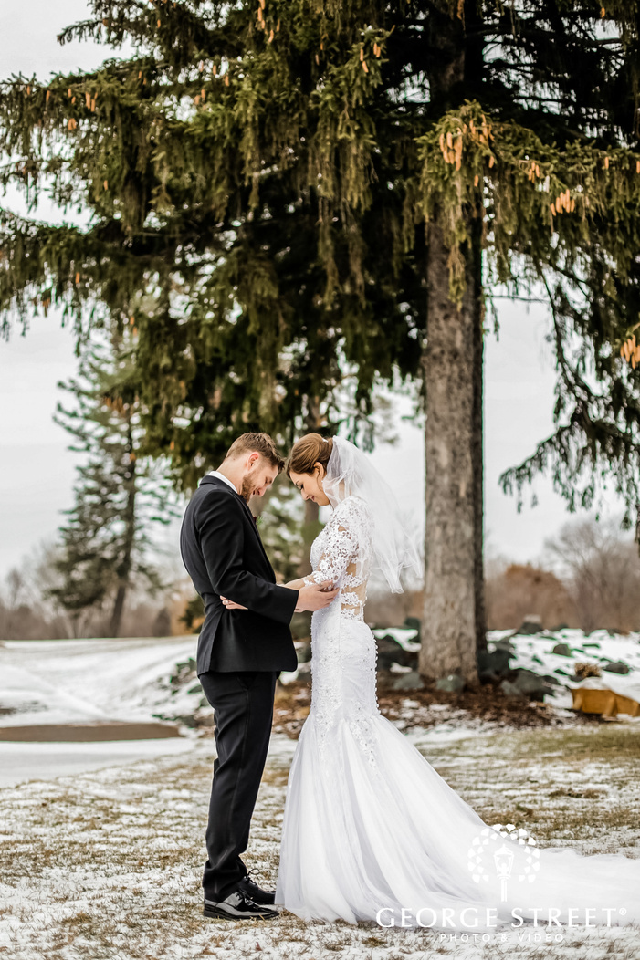 a beautiful bride in a mermaid style white wedding dress in a romantic embrace with the groom who is dressed in a black suit winter wedding photography