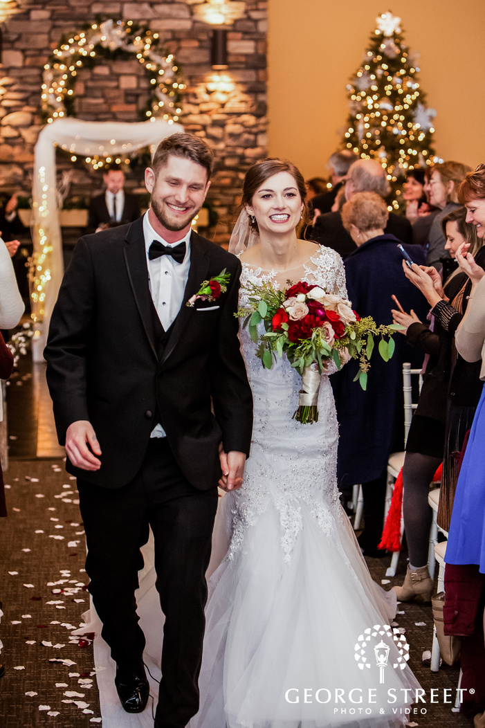 a beautiful bride in a wedding dress and a multicolor bouquet in her hand walking hand in hand up the aisle with the groom