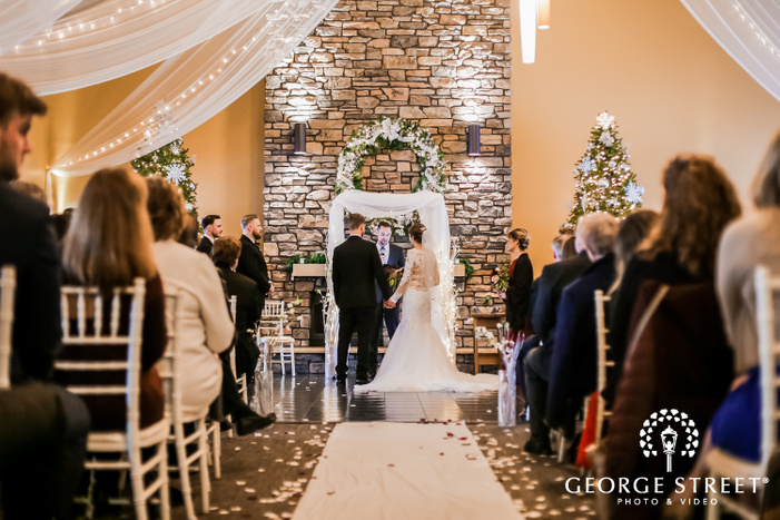 a beautiful couple getting married by the officiant at the altar in a hall decorated with drapes with decorated christmas trees and a fireplace in the backdrop