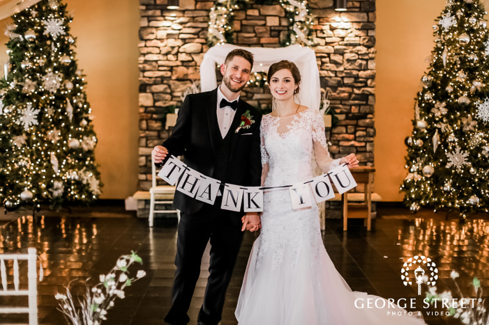 a beautiful couple in elegan twedding outfits holding a thank you sign in a hall with decorated christmas trees on both sides and a fireplace in the backdrop