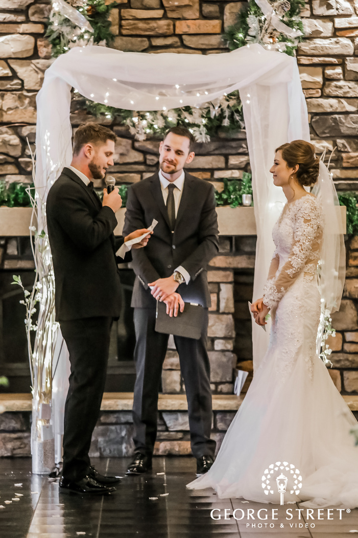 a handsome groom in a classy black wedding attire saying his vows while standing at the altar decorated with drapes the bride standing next to him