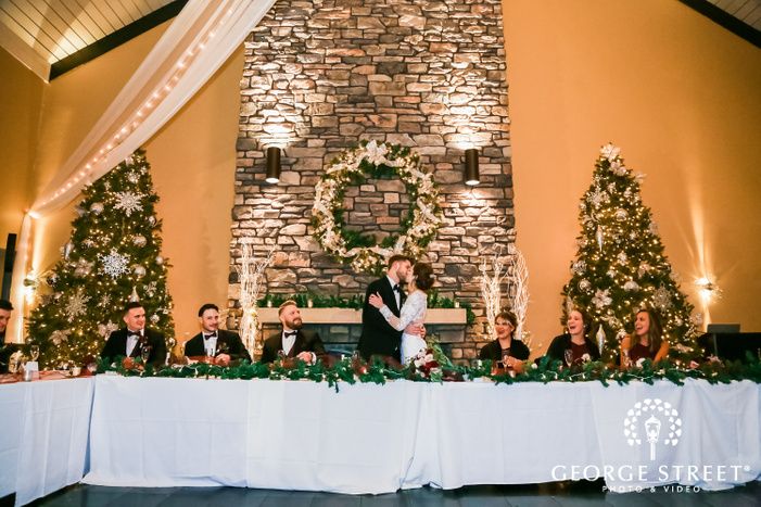 a newly wed couple in wedding attire kissing passionately while on a head table with cheering bridal party on both sides and a firerplace and decorated christmas trees in the backdrop