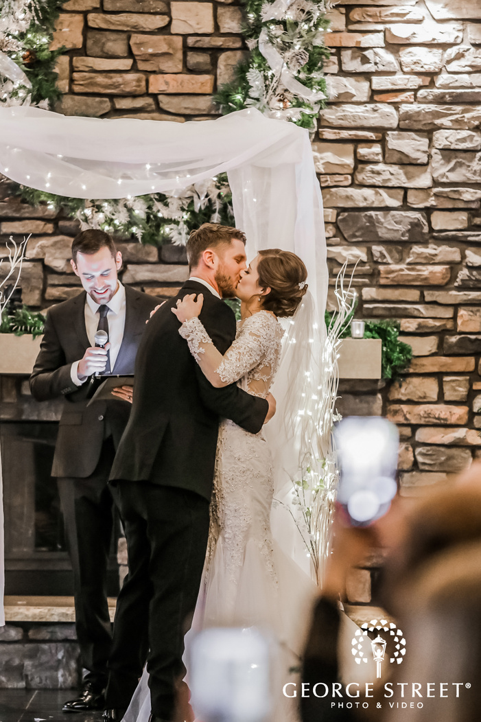 a photograph showcasing a just married coupel in elegant wedding dresses during their first kiss at the altar with the officiant standing in the backdrop