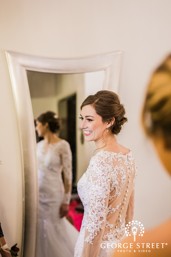 a smiling bride in a beautiful white wedding outfit in a room with a mirror with her reflection visible in it