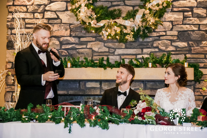 a smiling couple in elegant wedding attire listening keenly to the speech given by a groomsmen while sitting on the head table