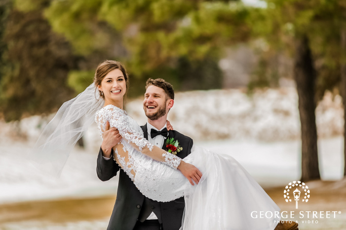 a smiling groom in a classy black wedding suit picking up the bride dressed in a white wedding outfit in his arms