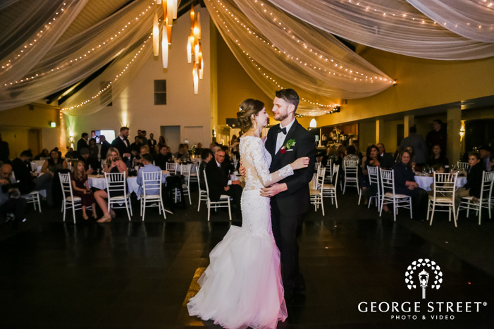 a smiling newly wed couple in elagant wedding attire during their first dance in a reception hall dcecorated elegantly with drapes with onlooking guests in the backdrop