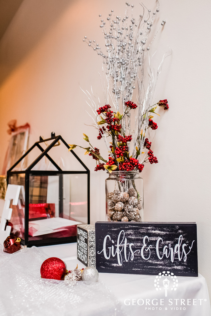 a wedding gifts table decorated with faux plants and pinecones