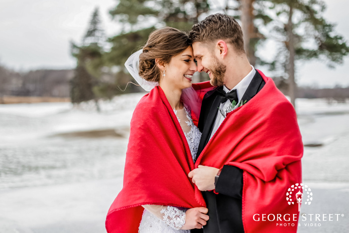 beautiful smiling couple in wedding outfits touching heads while being covered in a red shawl standing outside on a snow covered ground