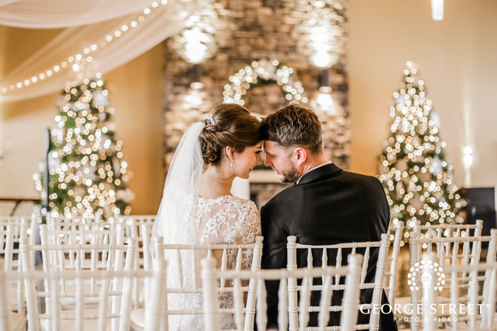 bokeh photograph of a couple in wedding outfits sitting on white chairs while touching heads with each other with christmas trees in the backdrop