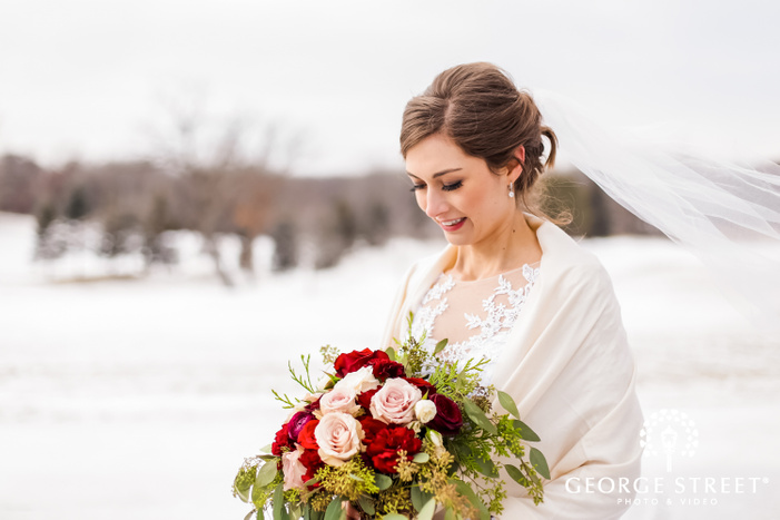 bokeh photograph showcasing a beautiful bride in a white wedding dress holding a bouquet of fresh assorted multicolor flowers