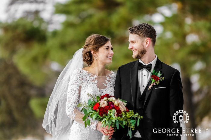 bokeh shot of an elegantly dressed smiling couple looking at each other while holding a multicolor rose bouquet