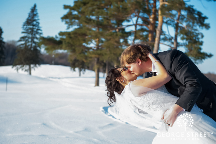 bokeh shot of of newly married couple kissing on the snow winter wedding photography