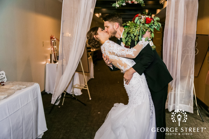 bride in a beautiful white wedding attire and a bouquet in her hand being kissed by the groom in a corridor