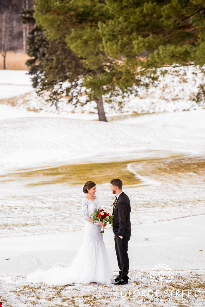 bride in an elegant white dress and a bouquet in her hand standiong with the groom on an open ground covered with snow