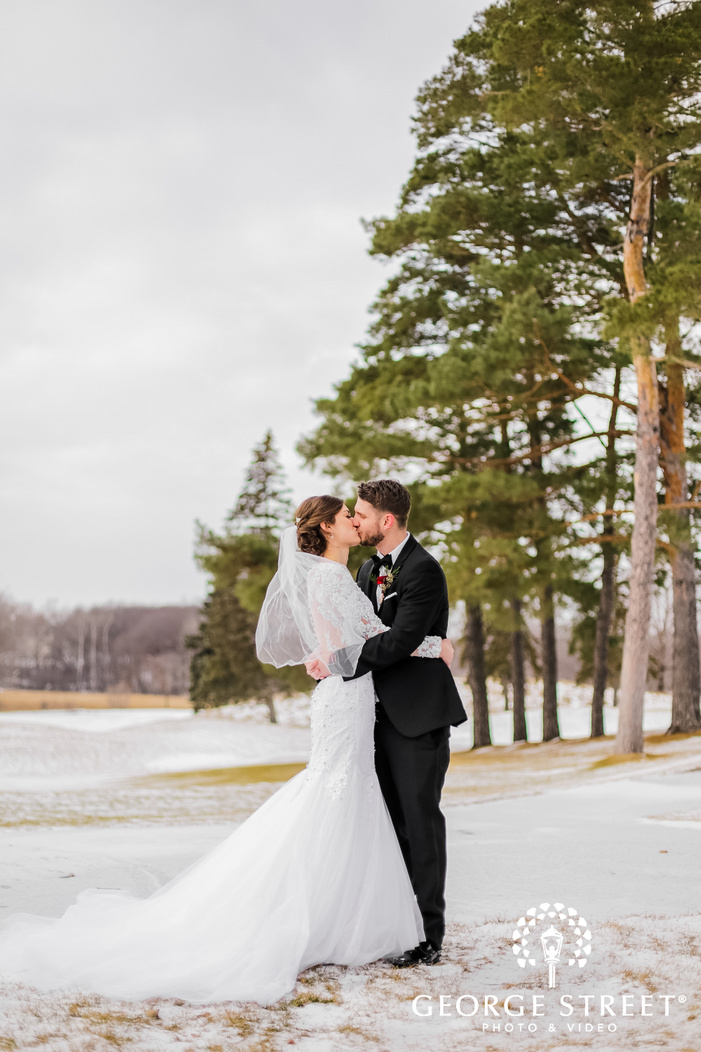elegantly dressed bride and groom kissing in the middle of an open snowy ground with trees in the backdrop
