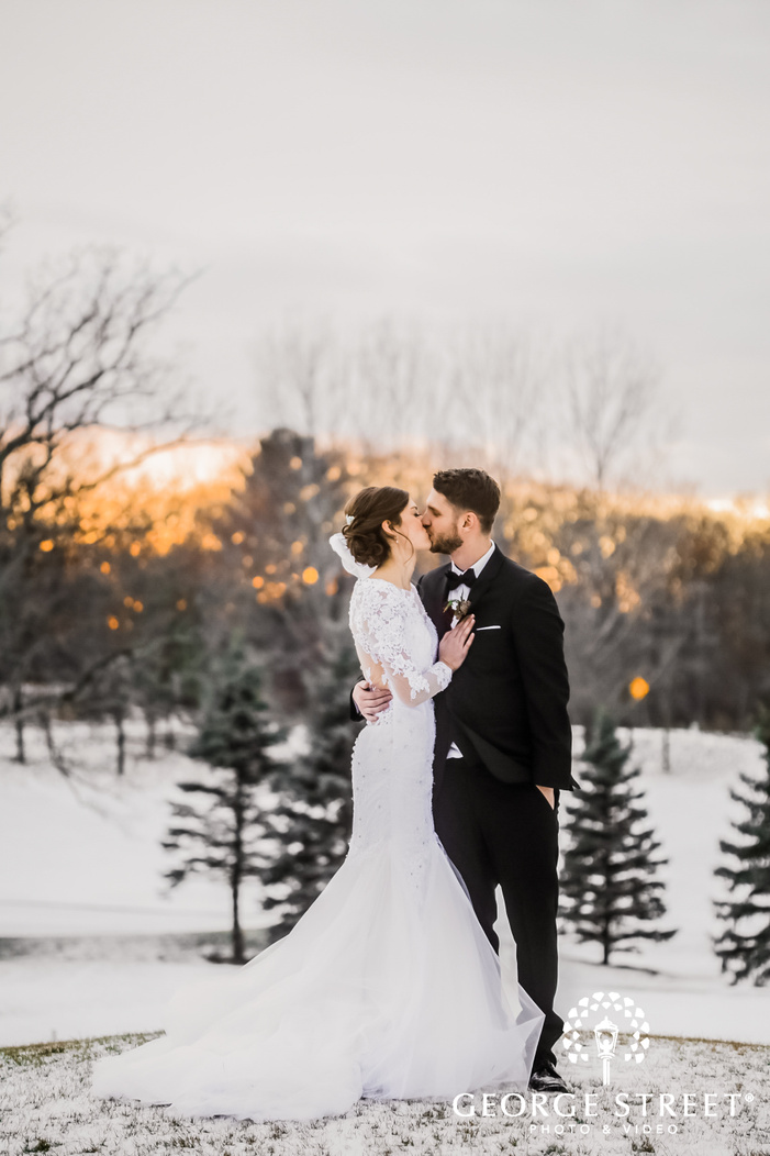 elegantly dressed bride in a white wedding attire kissing the groom who is in a black suit while standing on a ground covered in snow winter wedding photos