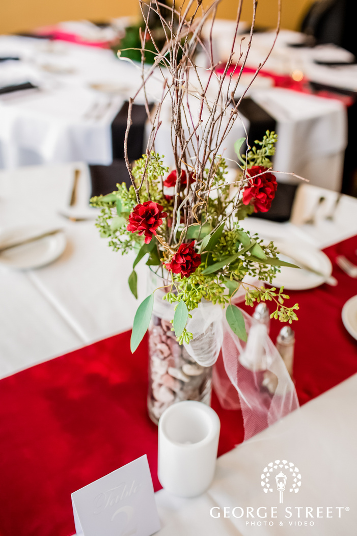 frame showcasing a fancy centerpiece with red flowers on a table top