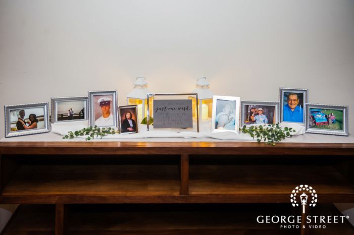 frame showcasing a table top decorated with framed portraits and candles wedding decor photography