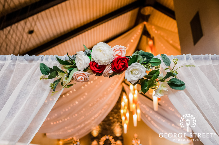 frame showcasing section of a dining hall decorated with fresh multicolor flowers and drapes winter wedding photography