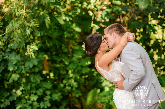 frame showcasing the bride and groom kissing passionately with foliage in the background