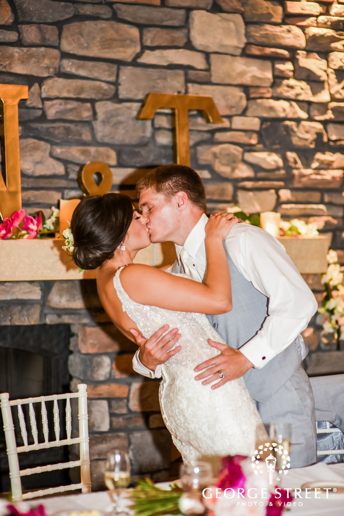 photograph of the bride and groom kissing passionately on the head table