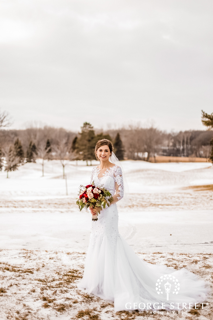 photograph showcasing a beautiful bride in a white wedding dress holding a bouquet of fresh assorted multicolor flowers standing on a snow covered ground