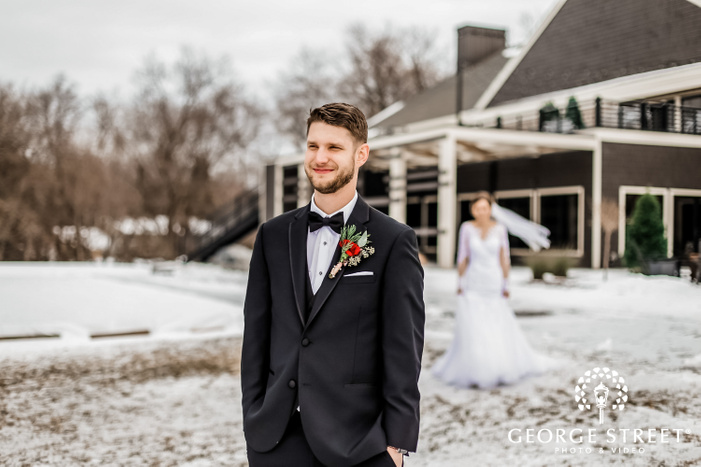 photograph showcasing a groom in a black suit waiting for the first look of the bride who is visible in the backdrop outside the wedding venue covered in snow