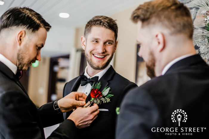 photograph showcasing a smiling groom in a black suit  getting help with his boutonniere by a groomsman