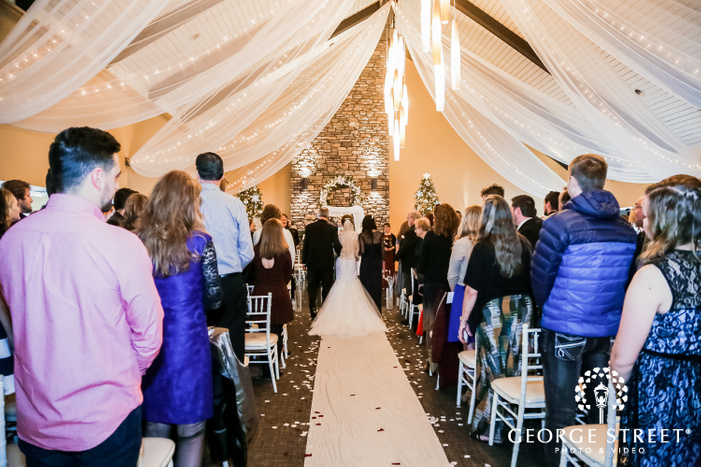 photograph taken from the back showcasing a beautiful bride being escorted down the aisle by her father with onlooking guests in a hall decorated with drapes