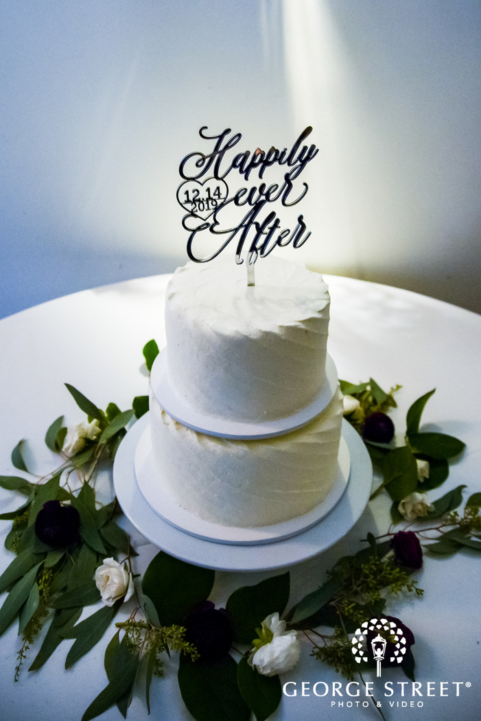 portrait shot of a two tiered white wedding cake with a topper reading happily ever after wedding photography