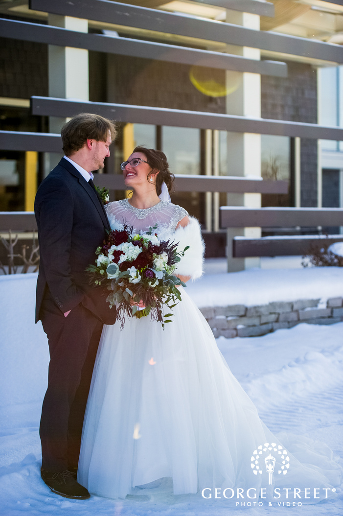 portrait shot of bride and groom smiling and looking at each other outside the wedding venue winter wedding photography
