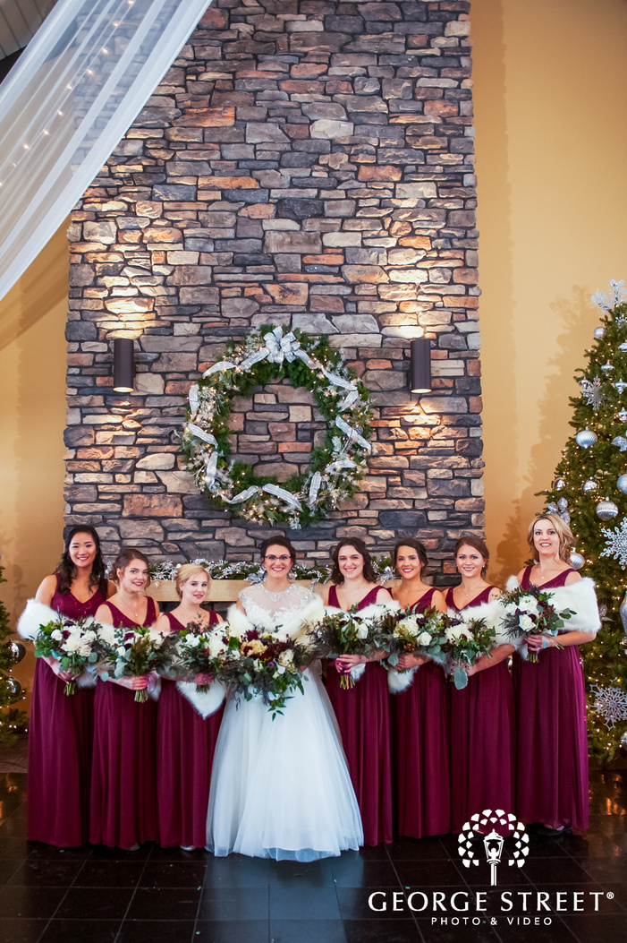 portrait shot of bride posing with her bridesmaids all holding a flower bouquets with a cobblestone wall section winter wedding photography