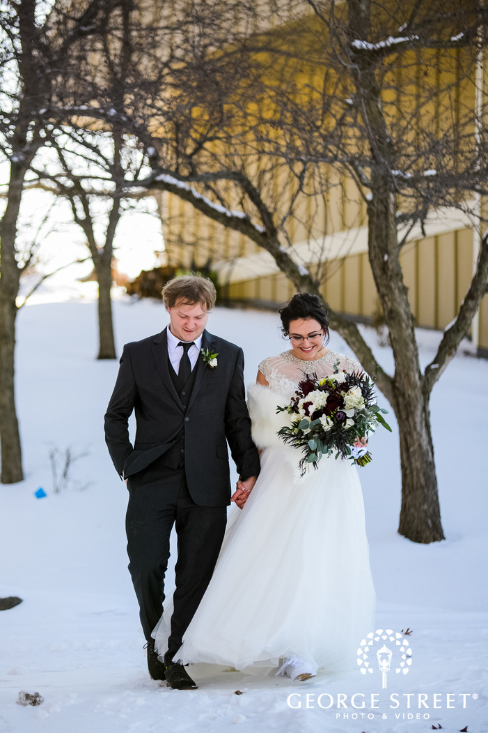 portrait shot of groom and bride holding hands and walking on snow outside the wedding venue