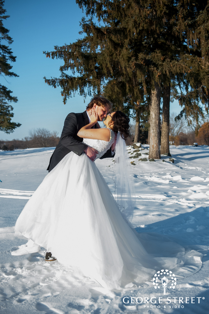 portrait shot of newly married bride and groom romantically posing on the snow winter wedding photography