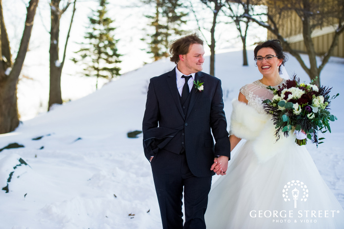 wide angle bokeh shot of groom and bride holding hands and walking on snow outside the wedding venue