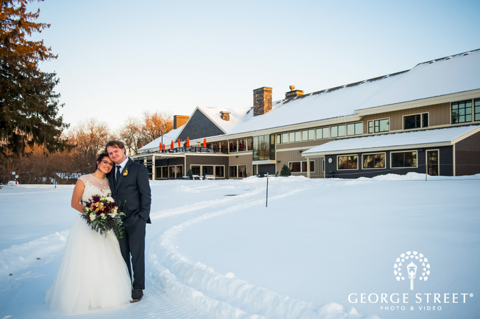 wide angle shot of bride and groom smiling and standing on the snow outside the wedding venue