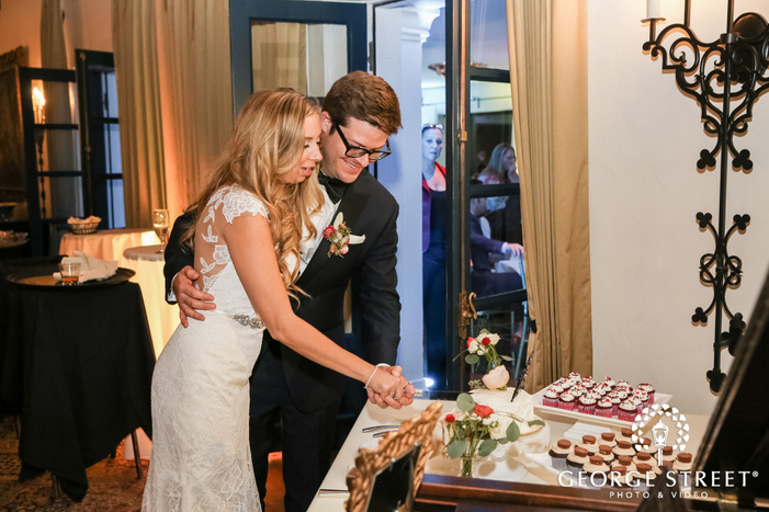 cheerful bride and groom cake cutting in reception wedding photo