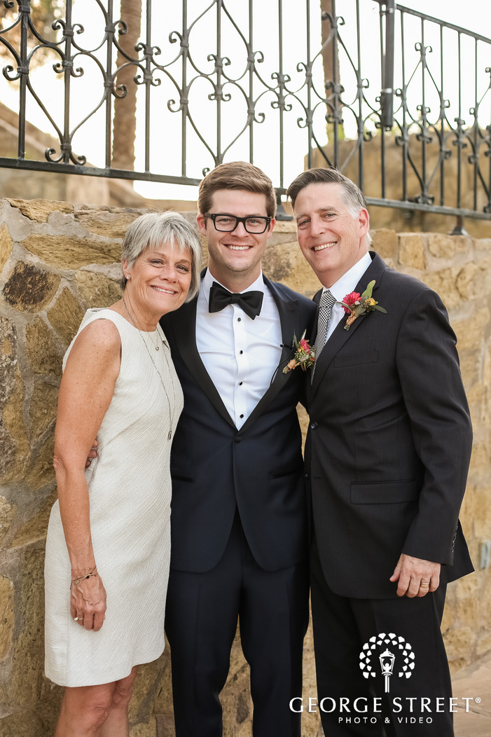 cheerful groom and parents near stone wall wedding photography