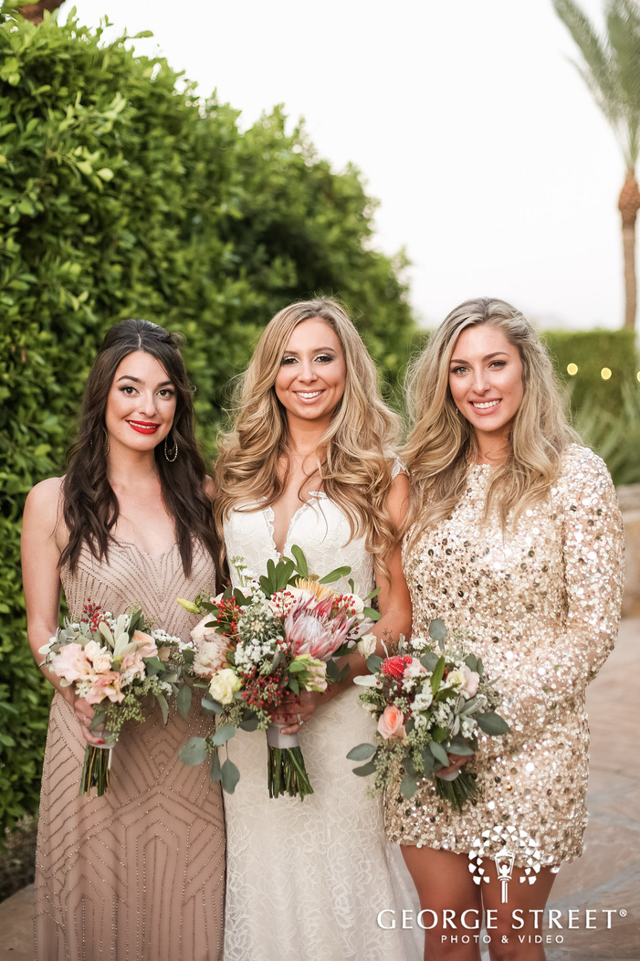 cheery bride and group near bushy wall wedding photography