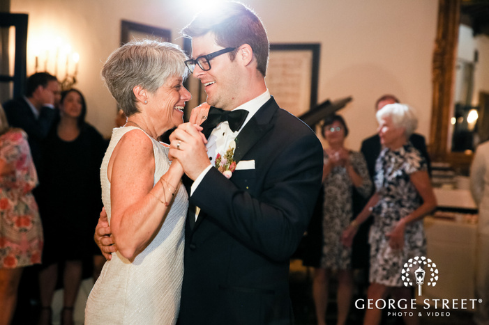 cheery groom and mother dance in reception wedding photo